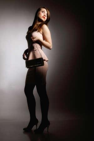 Full length  beautiful young woman with a bag handbag  Fashion photo dark gray background photo