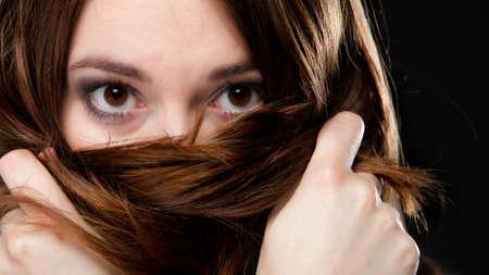 ojos marrones: Primer plano el retrato de una bella mujer cubre la cara por los pelos marrones largos