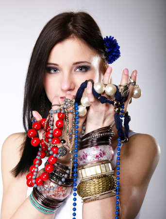 young woman in summer style with plenty of jewellery, beads in hands gray background photo