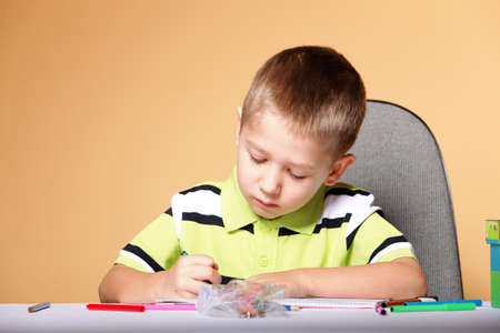 little boy drawing with color pencils on orange background Stock Photo - 19201657