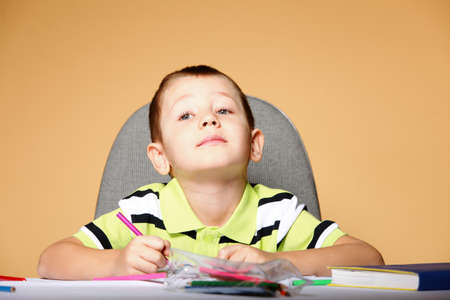 little boy drawing with color pencils on orange background Stock Photo - 19282546