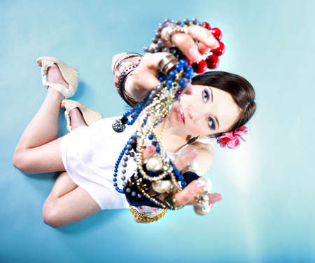 young woman in summer style with plenty of jewellery, beads in hands blue background photo