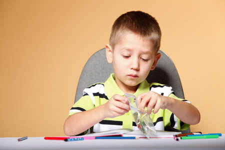 little boy drawing with color pencils on orange background Stock Photo - 19360068