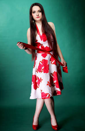 mmc: Full length young woman in summer flowery dress on green background fashion photo
