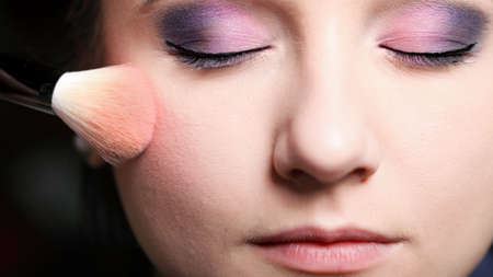 Makeup face young woman applying rouge blusher with brush photo