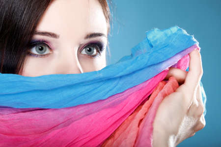 Young woman make up on eyes hides her face with multicolored shawl blue background Stock Photo - 19359982