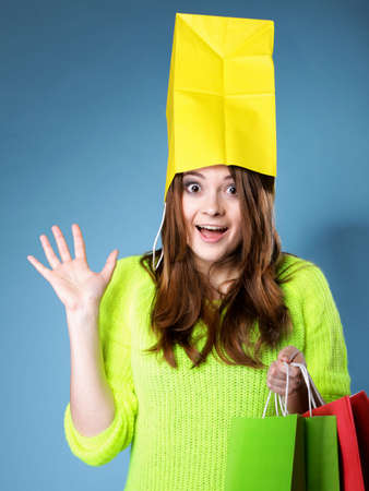 Surprised crazy woman bright vivid colour sweater with paper shopping bag on head blue background. Sales and discounts concept. photo