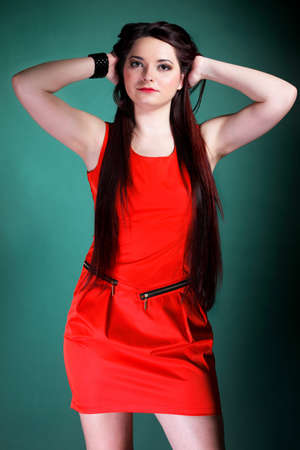 mmc: young woman long hair red dress on green background fashion photo