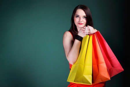 mmc: young woman long hair with paper multi coloured shopping bags on green background