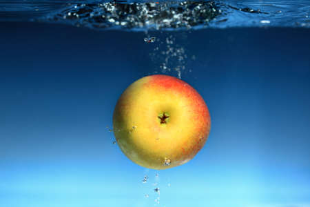 Yellow red apple in the water splash over blue background. Healthy food and active life. photo