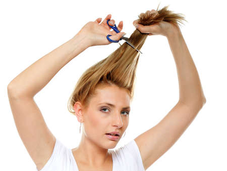 bad hair: Young blonde woman cutting her hair with scissors - unhappy expression, isolated on white background