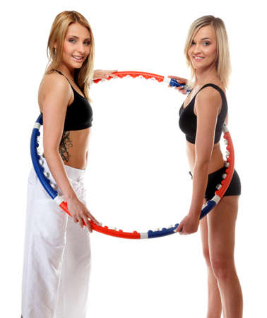 portrait of two girls exercising with hula hoops in gym. Fitness woman isolated on white photo