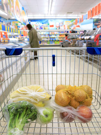 view of a shopping cart with grocery items at supermarket photo