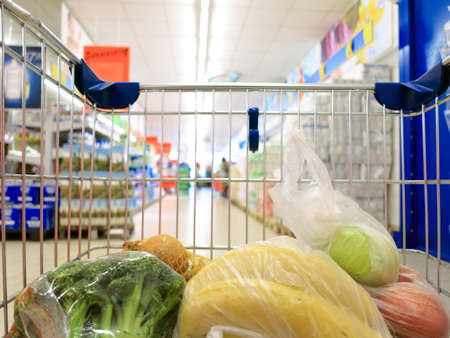 view of a shopping cart with grocery items at supermarket