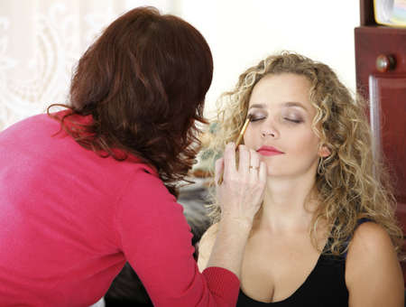 Make up artist applying make up to a fashion model indoor