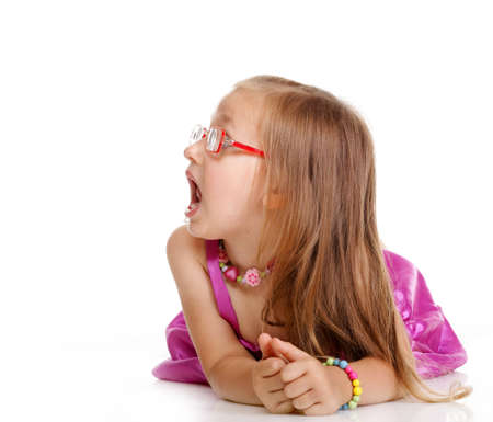 Little girl in glasses laying on floor looking to the side isolated over white