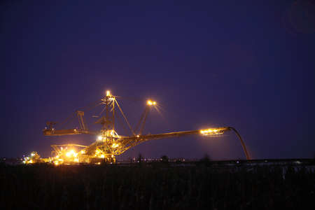 mine site: bucket wheel excavator digging for brown coal night view Poland extractive industry