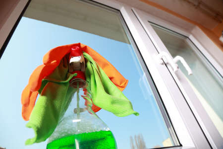 spring cleaning: Cleaning window using tools - rag and spray detergent. Spring cleaning concept