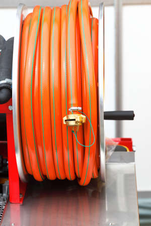rolled up of orange plastic hose industrial detail photo