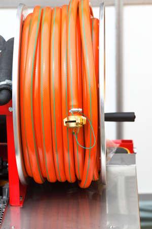 vulcanization:  rolled up of orange plastic hose industrial detail