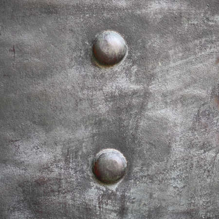 Black grunge metal plate or armour texture with rivets as background photo