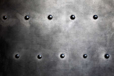 Black grunge metal plate or armour texture with rivets as background Stock Photo