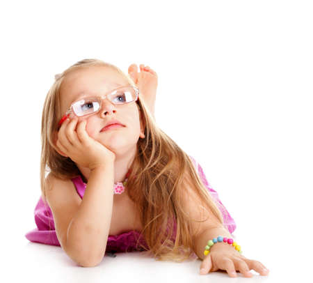 Portrait of a dreaming little girl in glasses laying on floor, isolated over white photo