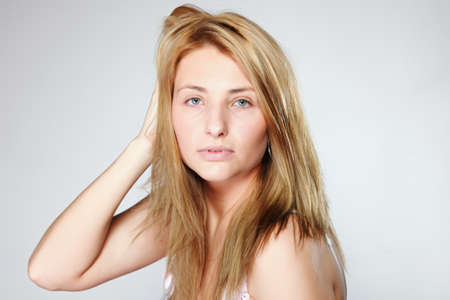 Attractive blonde woman with no make up gray background Stock Photo