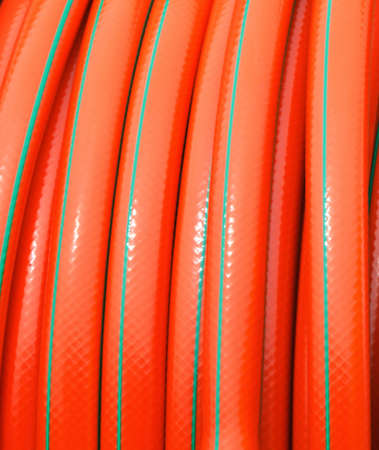 vulcanization:  rolled up of orange plastic hose industrial detail as background texture