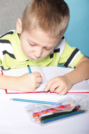 little boy drawing with color pencils on blue background photo