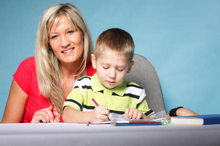mother and son drawing together, mom helping with homework blue background photo
