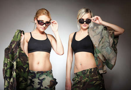 Two women in military clothes and sunglasses army girls on gray background photo