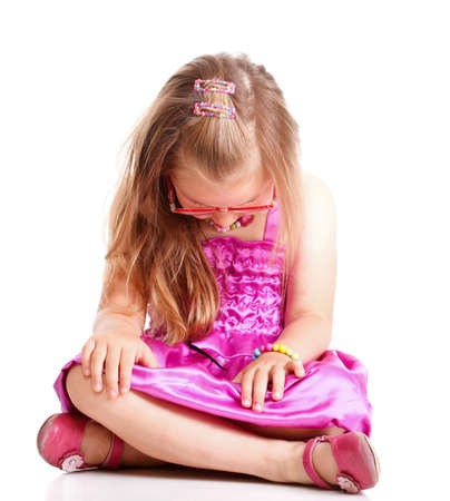 morose: Upset little girl sitting on floor with head lowered isolated on white