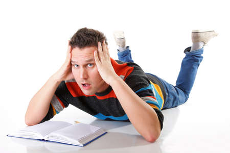 tired college student with book after hard work for exam on white background photo