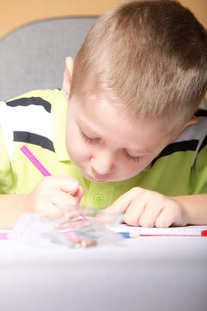 little boy drawing with color pencils on orange background photo