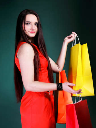 mmc: young woman long hair with paper multi coloured shopping bags on green background. Sales and discounts concept.