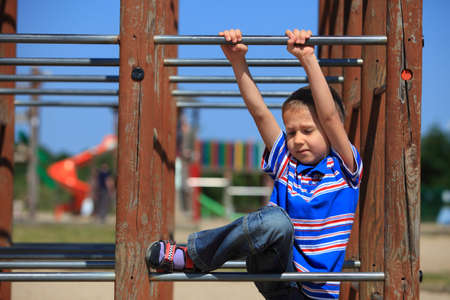 child in playground kid in action boy play on leisure equipment climbing photo