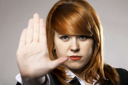 to restrain: Young business woman making stop gesture sign on gray background