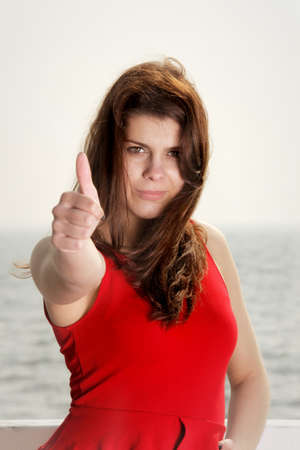young woman in red dress on the pier in the morning thumb ub gesture, summer holiday photo