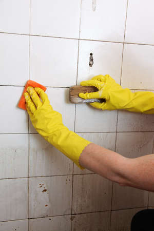 gloved hand cleaning dirty old tiles with brush in a bathroom photo