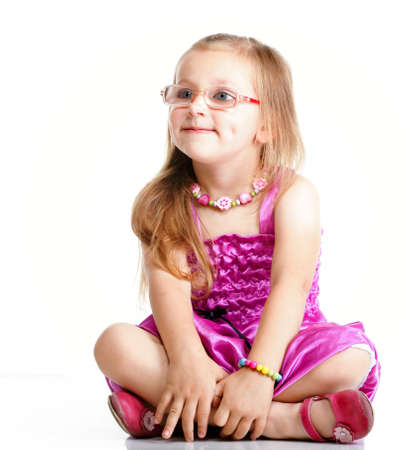 cute little girl sitting on floor and smiling, studio shot isolated on white background photo