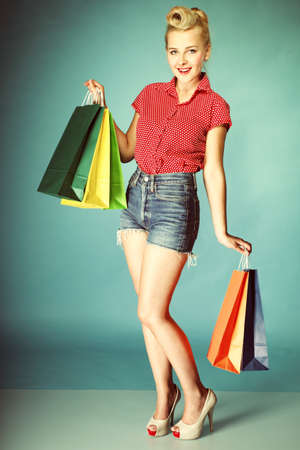 Retro style. Full length young woman in red dotted shirt and shorts with colourful shopping bags isolated on blue background Stock Photo - 20328074