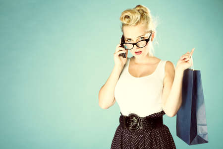 Retro style. Young woman pinup girl in glasses with shopping bag talking on cell phone blue background Stock Photo - 20327644