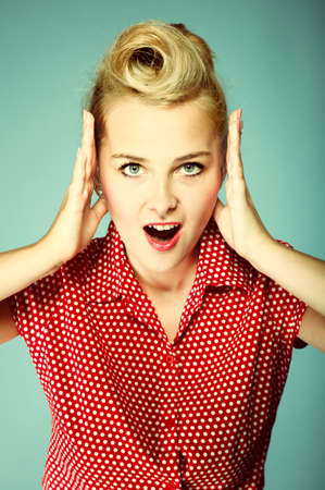 surprised woman face, beautiful girl in retro style holding her head in amazement and open-mouthed blue background photo