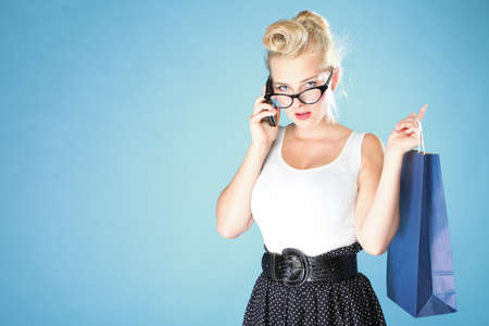 Retro style. Young woman pinup girl in glasses with shopping bag talking on cell phone blue background photo