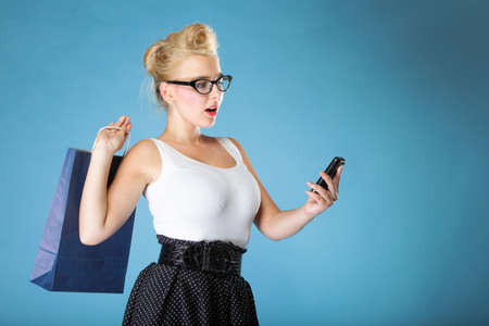 Retro style. Young woman with shoppihg bag has reaction of surprise as she reads a message on her mobile phone, blue background photo