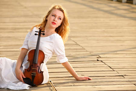 The blonde girl music lover on pier with a violin. Love of music concept. photo