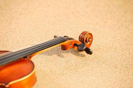 of mozart: Violin on sandy beach. Love of music concept Stock Photo