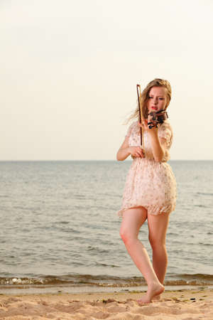 The blonde girl music lover on beach playing the violin. Love of music concept. photo