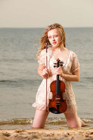 The blonde girl music lover on beach with a violin. Love of music concept. photo